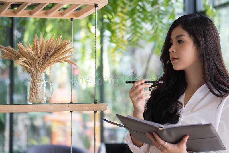 Hållande anteckningsbok för affärskvinna på kontoret den unga kvinnlign entrepren royaltyfria bilder