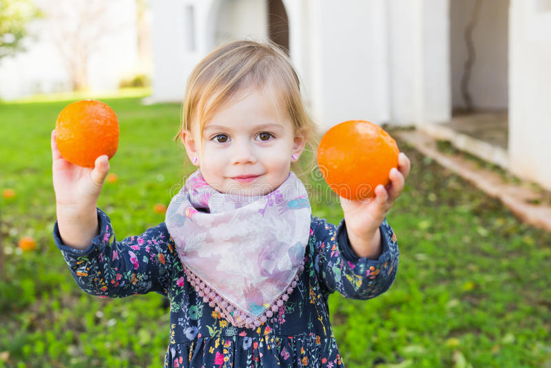 Hållande apelsiner för liten flicka i trädgården arkivfoton