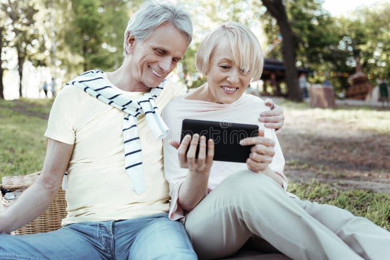 Hållande apparat för charmig blond kvinna i båda händer royaltyfri foto