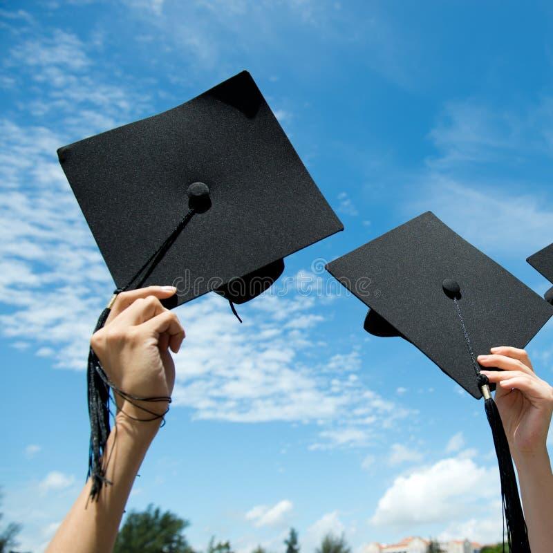 Hållande avläggande av examenhattar royaltyfri fotografi