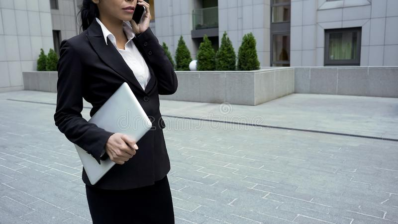 Hållande bärbar dator för affärskvinna och samtal på mobiltelefonen, personlig assistent till vd:n royaltyfria bilder