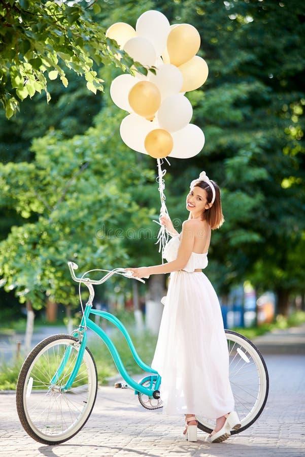 Hållande baloons för lycklig kvinna, medan rida cykeln royaltyfria foton