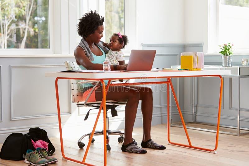 Hållande barn för kvinna som hemma använder datoren, når att ha övat arkivfoton