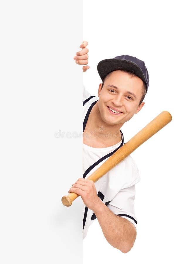 Hållande baseballslagträ för idrottsman nen bak en panel royaltyfri fotografi