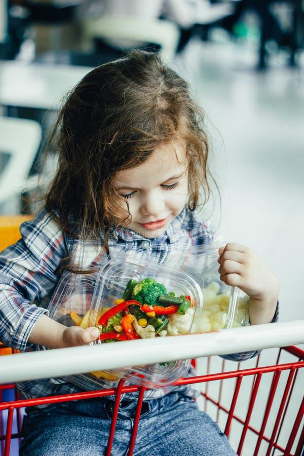 Hållande behållare för gullig flicka med sund mat i armar som sitter i en shoppingvagn royaltyfria bilder