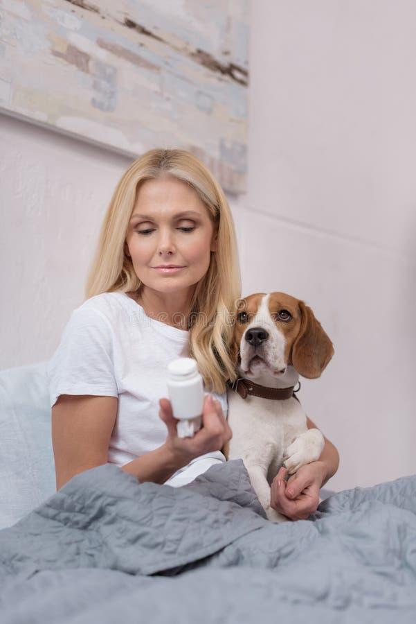 hållande behållare för sjuk kvinna med medicin och kramahunden, medan sitta royaltyfria bilder