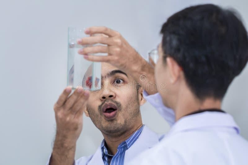 Hållande behållare för stilig professor i det vita följet Dem som ser fisken arkivbilder