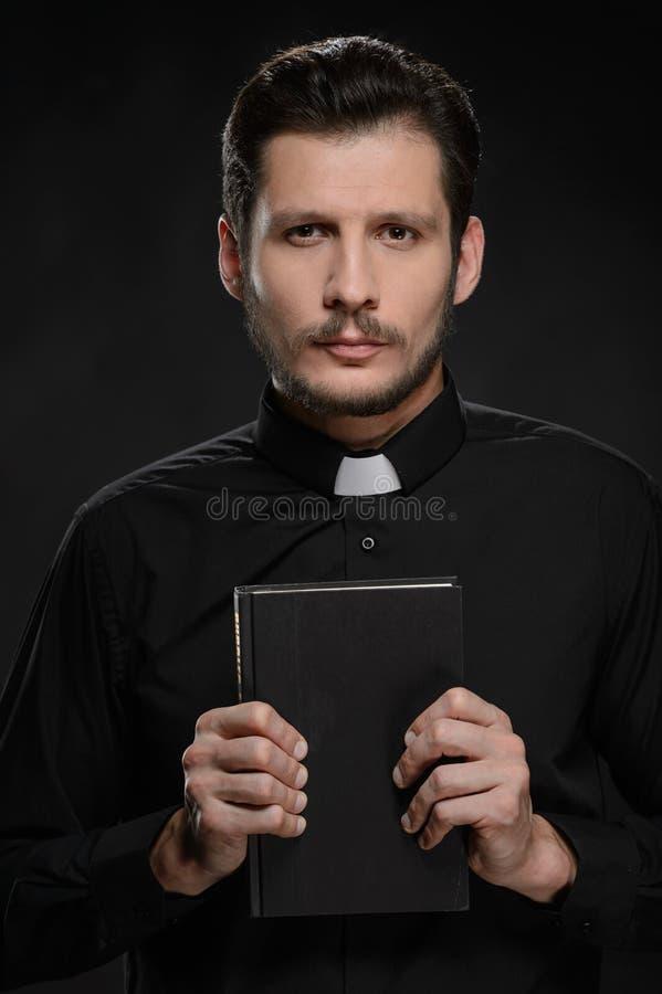 Hållande bibel för präst royaltyfri bild
