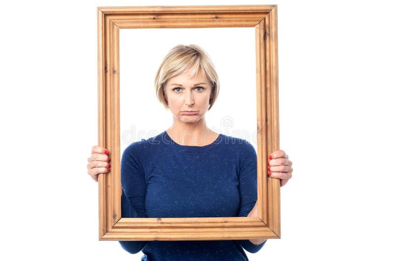 Hållande bildram för ledsen kvinna arkivbild