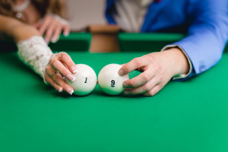 Hållande billiardbollar för brud och för brudgum royaltyfria foton