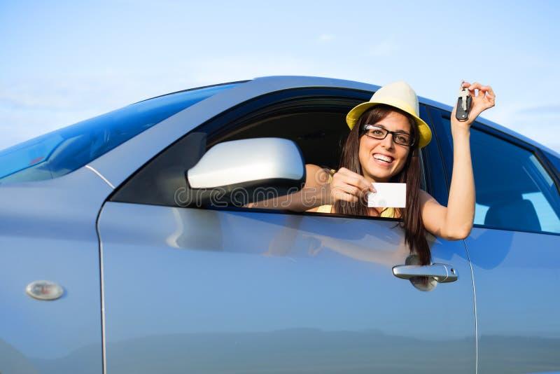 Hållande biltangenter för lyckad kvinnlig chaufför och körningslicens royaltyfri fotografi