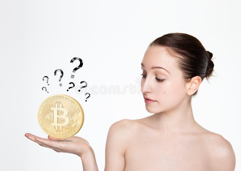 Hållande bitcoin för flicka på hennes hand med fråga fotografering för bildbyråer