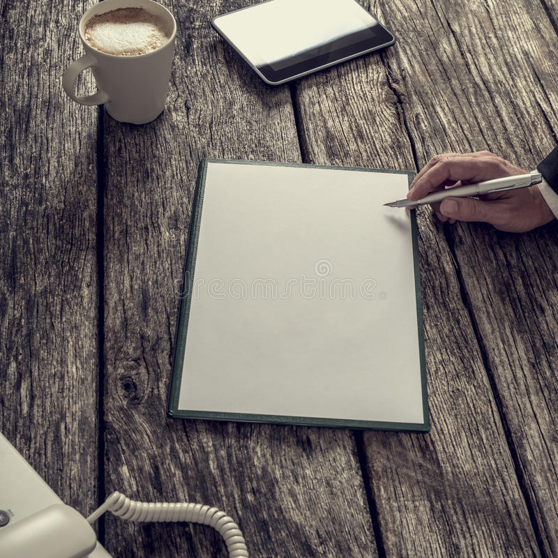 Hållande bläckpenna för affärsman omkring som ska skrivas på en tom vit piec royaltyfri foto