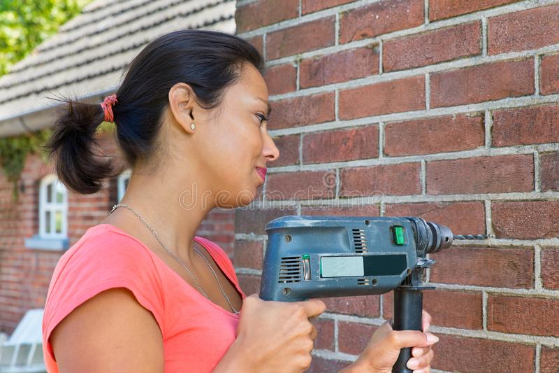 Hållande borrandemaskin för kvinna på tegelstenväggen arkivbild