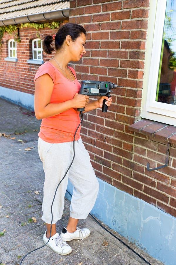 Hållande borrandemaskin för kvinna på tegelstenväggen royaltyfri fotografi