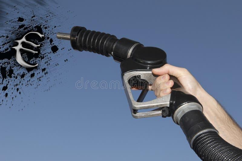 Hållande bränsleslang för hand som besprutar bensinolja i formen av eurosymbolet arkivbild