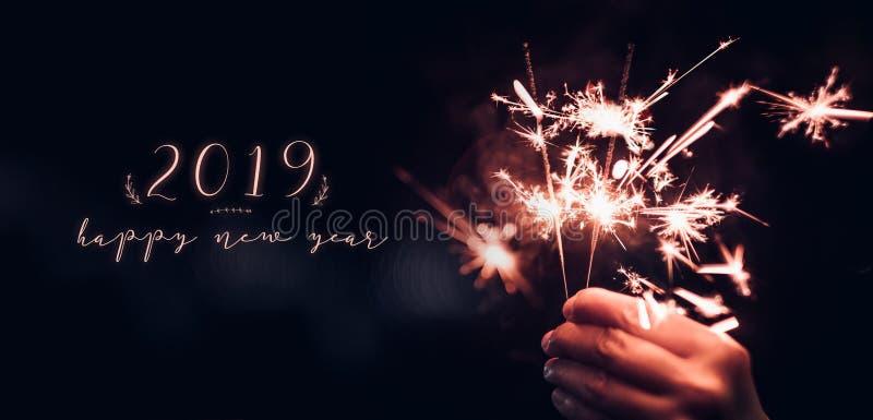 Hållande brinnande tomteblosstryckvåg för hand med det lyckliga nya året 2019 på royaltyfri fotografi