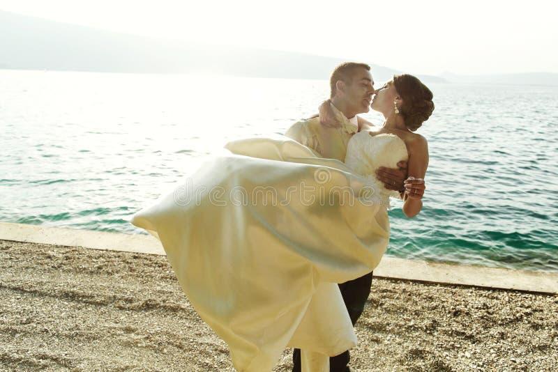 Hållande brud för lycklig stilig brudgum i hans armar på stranden på sunse royaltyfri foto