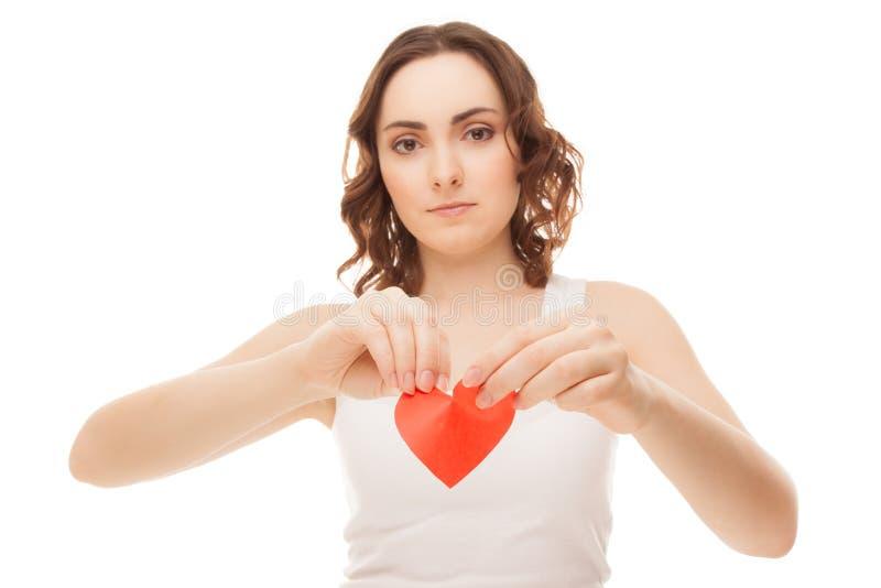 Hållande bruten pappers- röd valentinhjärta för attraktiv ung flicka