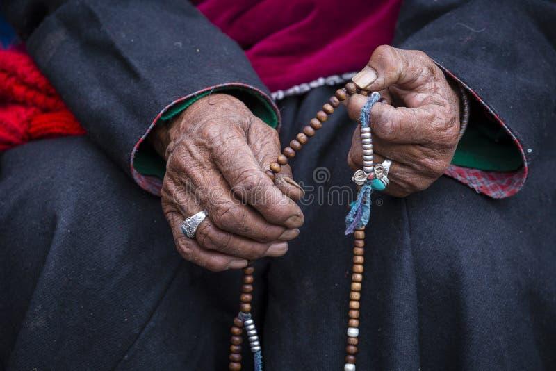 Hållande buddistisk radband för gammal tibetan kvinna i den Hemis kloster, Ladakh, Indien Hand och radband, slut upp royaltyfri bild
