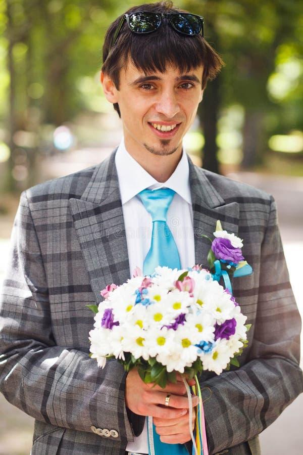 Hållande bukett för attraktiv brudgum och le på bakgrunden p royaltyfri foto