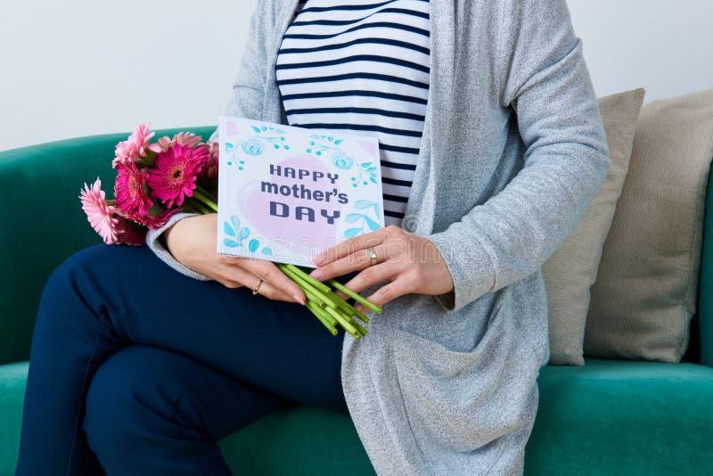Hållande bukett för barnmoder av sammanträde för kort för hälsning för dag för gerberatusensköna- och moder` s på en soffa royaltyfria bilder