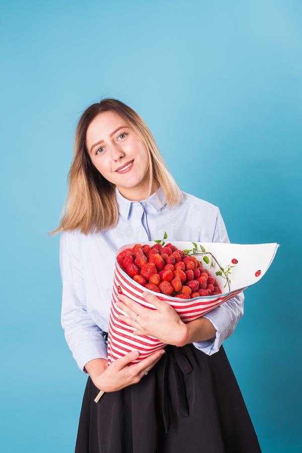 Hållande bukett för härlig kvinna som göras av jordgubben royaltyfria bilder