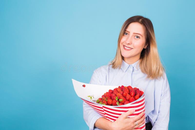 Hållande bukett för härlig kvinna som göras av jordgubben arkivfoto