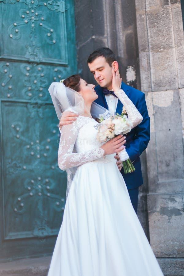 Hållande bukett för härlig stilfull ung brud och för stilig brudgum av rosor som ansikte mot ansikte utomhus kramar slottdörrbakg royaltyfri fotografi