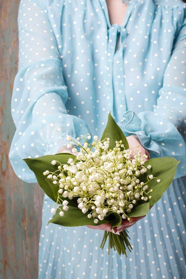 Hållande bukett för kvinna av liljekonvaljblommor royaltyfria bilder