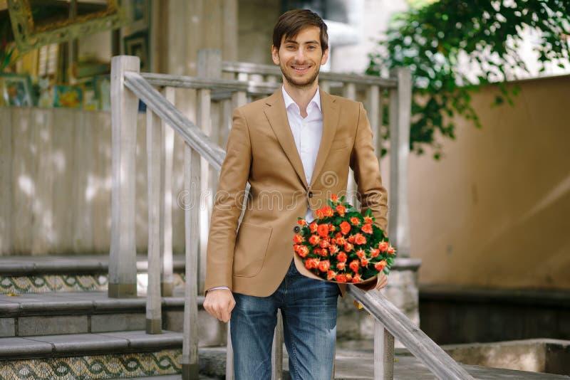 Hållande bukett för stilig man av rosor som talar som är lycklig på telefonen arkivbild