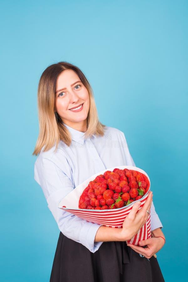 Hållande bukett för ung kvinna av jordgubbar på blå bakgrund fotografering för bildbyråer