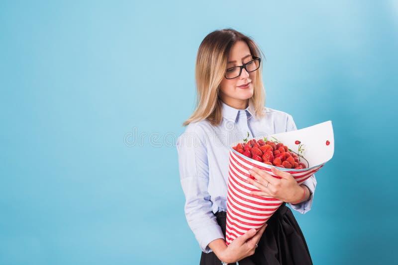 Hållande bukett för ung kvinna av jordgubbar på blå bakgrund royaltyfri bild
