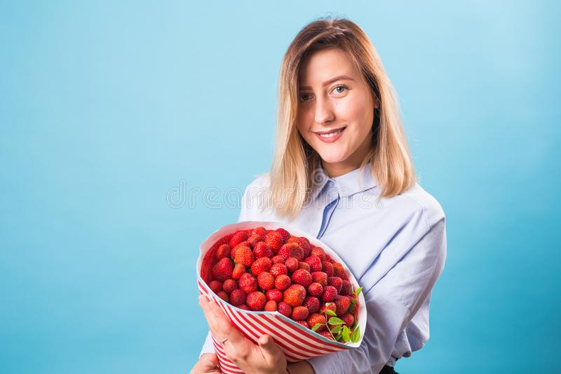 Hållande bukett för ung kvinna av jordgubbar på blå bakgrund royaltyfri fotografi