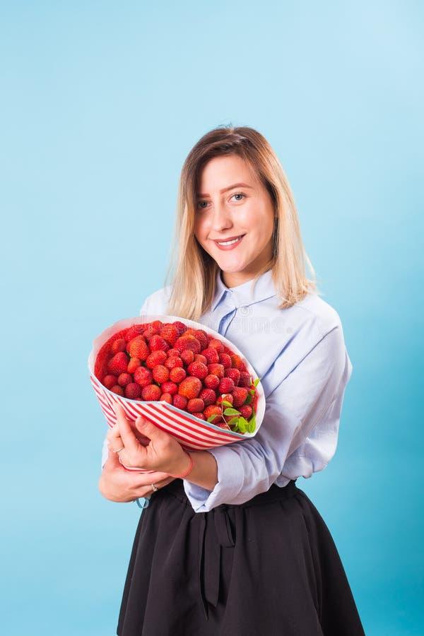 Hållande bukett för ung kvinna av jordgubbar på blå bakgrund royaltyfria foton