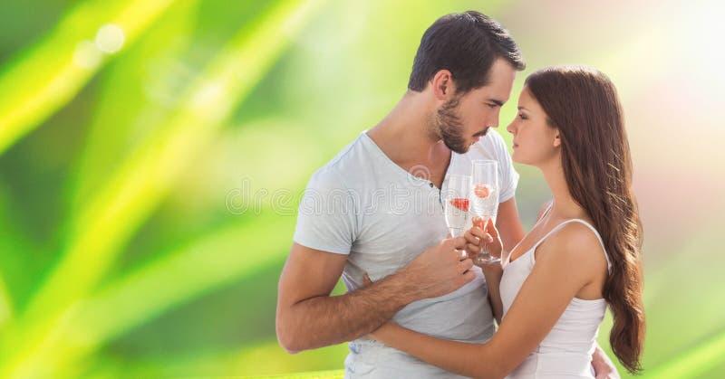 Hållande champagneflöjter för passionerade par, medan omfamna över suddighetsbakgrund royaltyfri bild