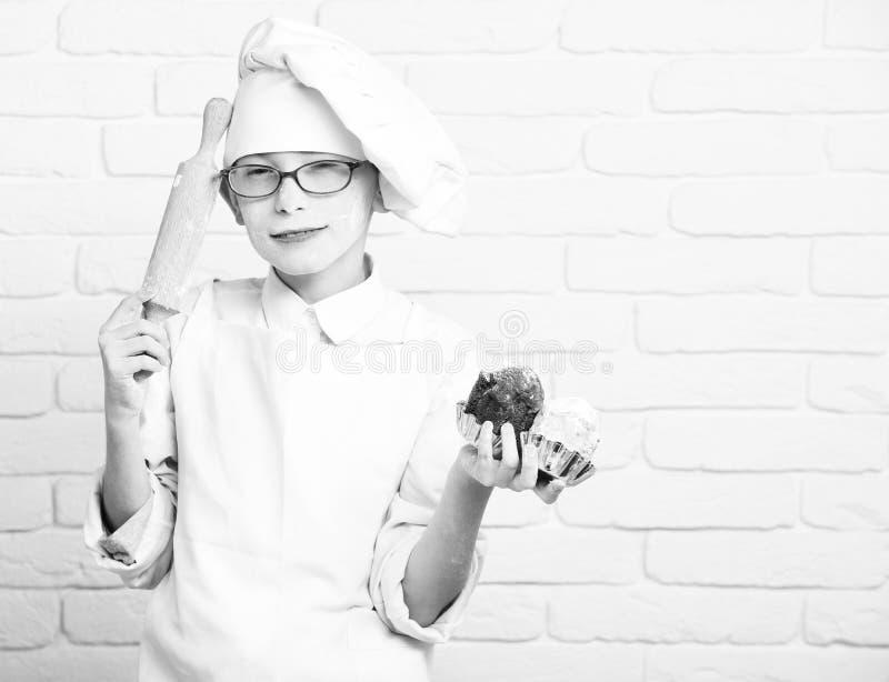 Hållande chokladkakor och kavel på bakgrund för tegelstenvägg, kopieringsutrymme Nedfläckad gullig kockkockpojke arkivbilder