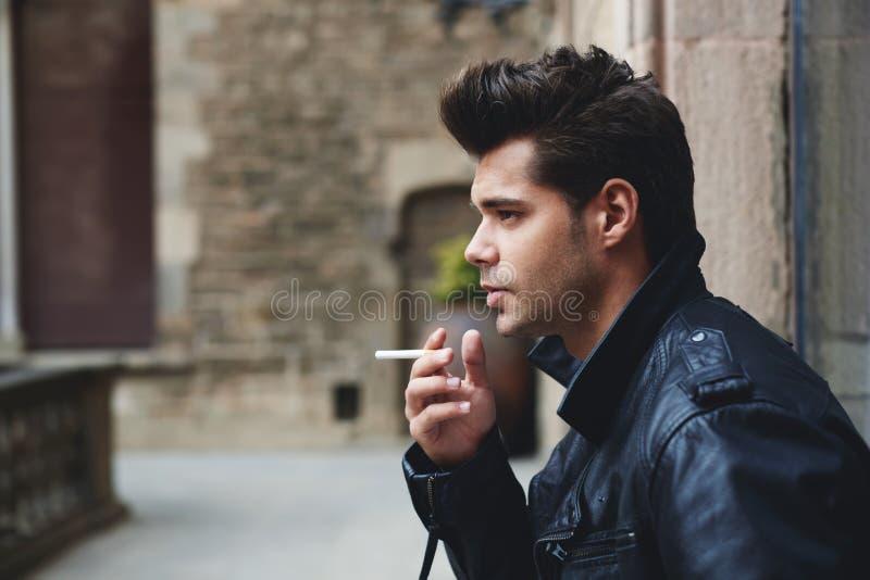 Hållande cigarett för stilig manlig modell i handen som ser eftertänksam och allvarlig royaltyfri bild