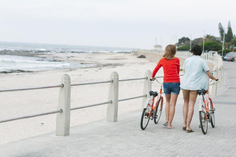 Hållande cykel för Caucasian par, medan gå på trottoar nära promenad fotografering för bildbyråer