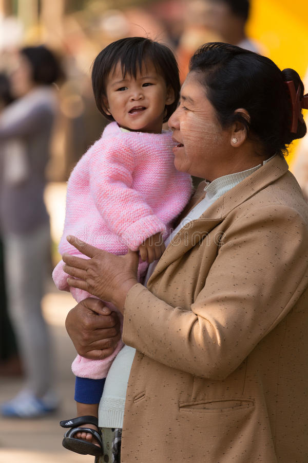 Hållande daugther för Burmesemoder royaltyfria bilder