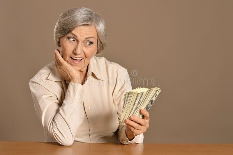 hållande dollar för åldrig kvinna arkivbilder