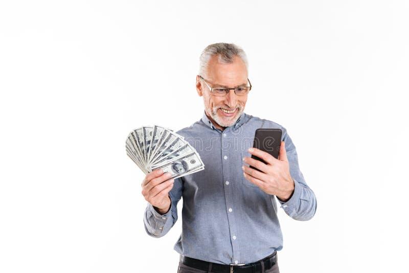 Hållande dollar för mogen man och isolerad användasmartphone royaltyfria foton