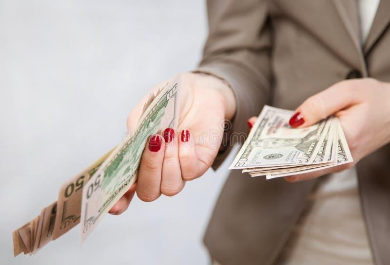 Hållande dollar för oigenkännlig affärskvinna arkivbilder