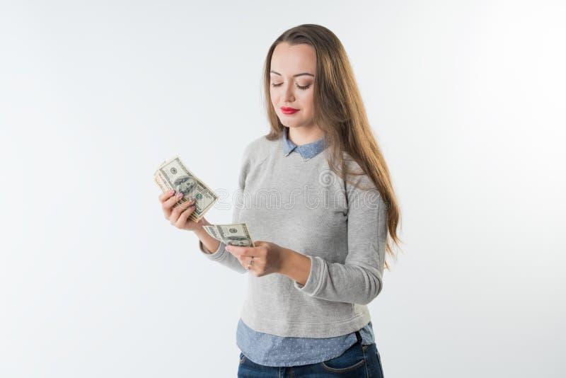 Hållande dollarkassa för ung kvinna som räknar pengar arkivfoto