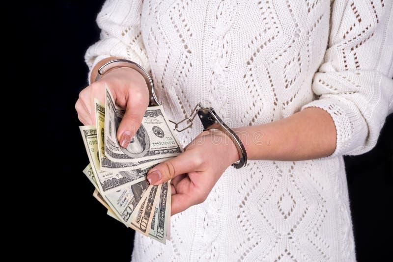 hållande dollarräkningar för kvinna i handbojor royaltyfri foto