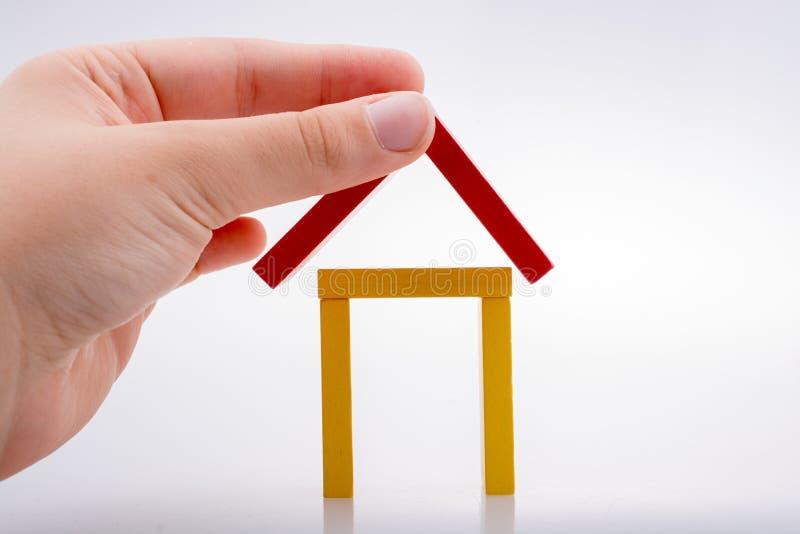 Hållande dominobricka för hand som bildar ett hus arkivfoto