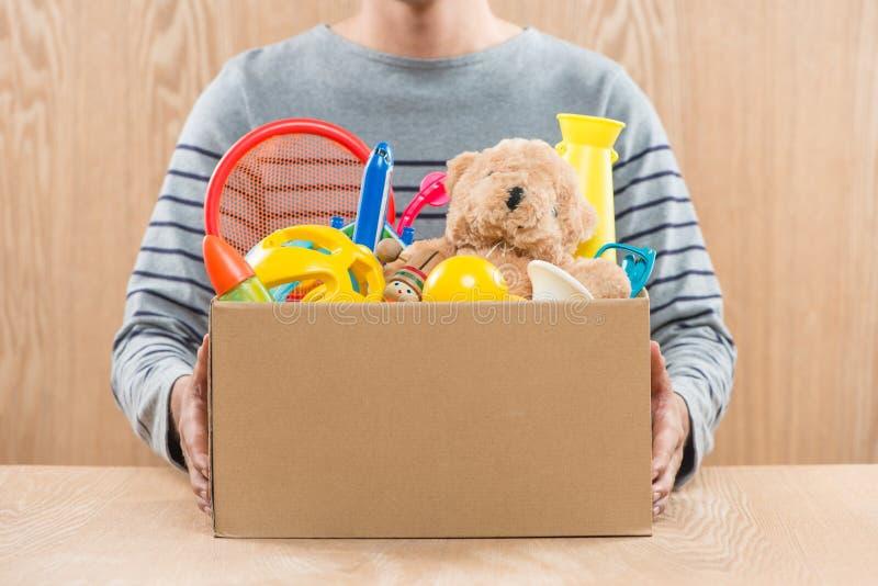 Hållande donationask för manlig volontär med gamla leksaker arkivbilder