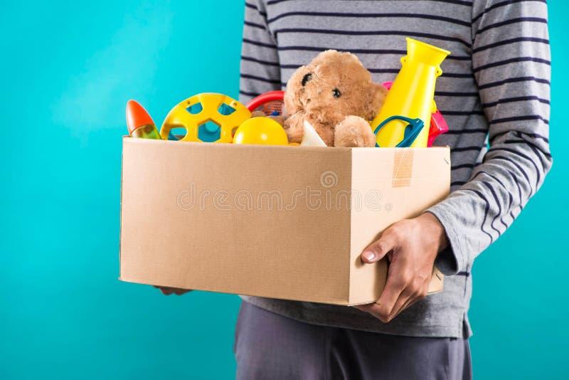 Hållande donationask för manlig volontär med gamla leksaker arkivfoton