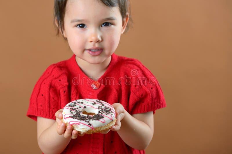 Hållande donuts för liten flicka arkivbilder