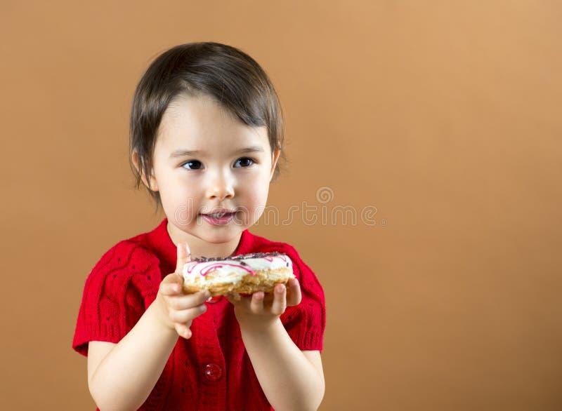 Hållande donuts för nätt liten flicka på brun bakgrund royaltyfri foto